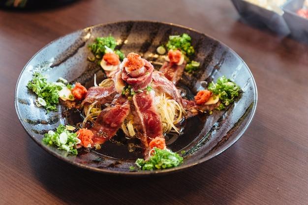 Rare tranche a5 wagyu avec oignons verts émincés, daikon à la sauce shoyu.