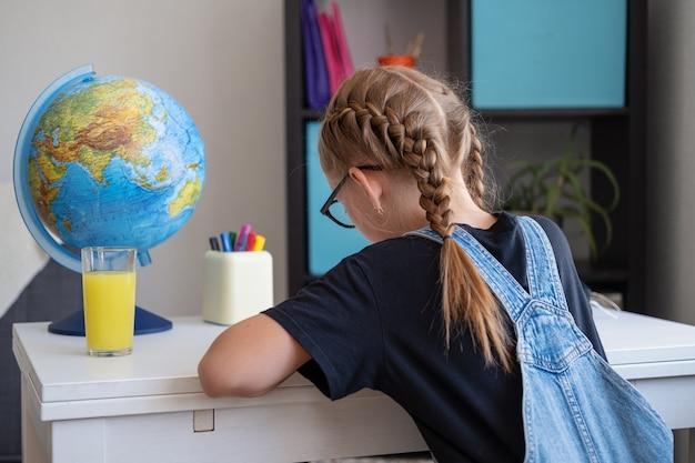 Rare vue d'une fille rousse caucasienne à lunettes étudiant à la maison, faire ses devoirs. l'écriture. intello. concept d'éducation à distance. quarantaine. retour au concept de l'école.