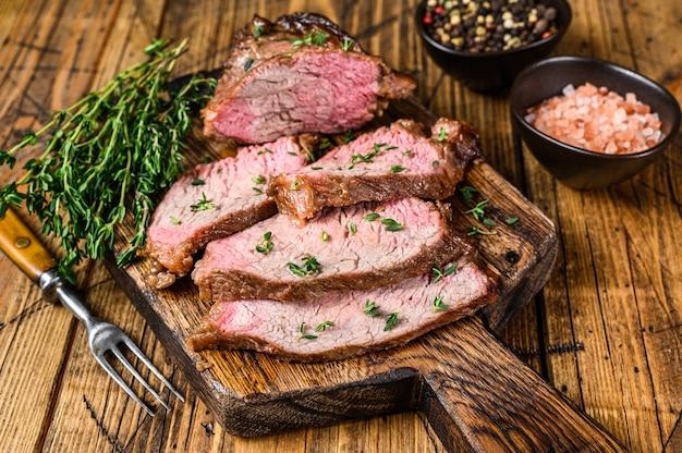 De rares tranches de rosbif surlonge à trois pointes de steak bbq sur une planche à découper en bois.