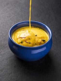 Ras malai ou rossomalai est un dessert du bengale, en inde. c'est un gâteau au fromage riche sans croûte, avec des garnitures au safran ou au kesar et à la pistache. servi dans un bol sur fond en bois ou coloré
