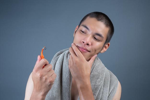 Rasage beau mec rasé sur le visage sur gris