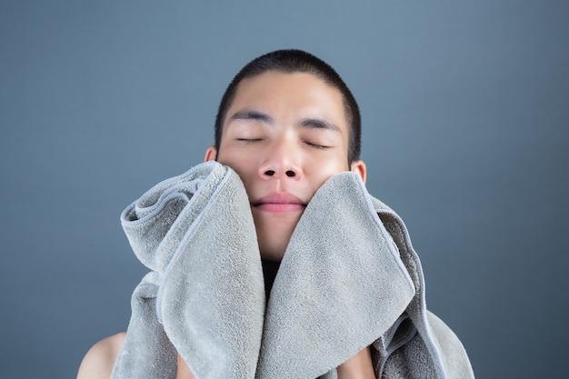 Rasage de beaux jeunes hommes avec une serviette sur fond gris