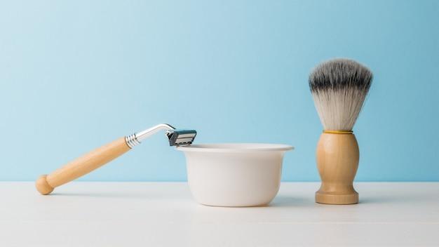 Un rasoir et une brosse avec des manches en bois et un bol en mousse sur une table blanche.