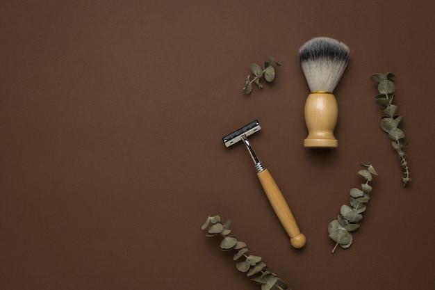Rasoir et brosse vintage et brindilles d'eucalyptus sur fond marron. espace pour le texte. accessoires pour hommes pour le soin de l'apparence. mise à plat.