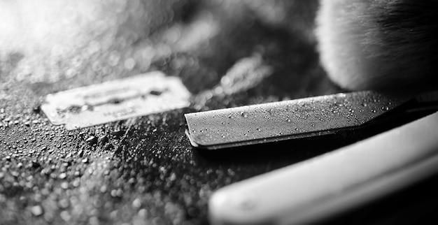 Un rasoir dangereux et une lame en métal sur la table. accessoires de rasage pour hommes. rasoir brutal pour les vrais hommes. gouttes d'eau sur la table.