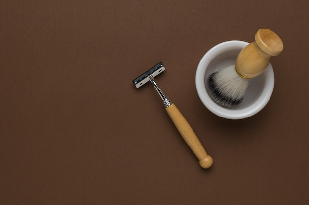 Un rasoir élégant, une brosse et un bol blanc sur fond marron. mise à plat.
