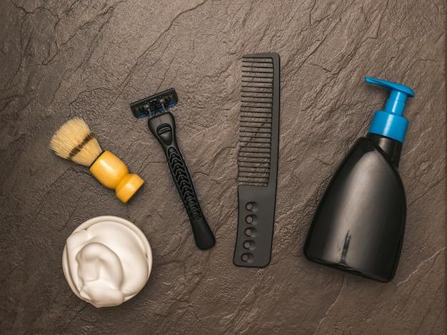 Rasoir pour hommes, mousse à raser et peigne sur une table en pierre. set pour le soin du visage d'un homme. mise à plat.