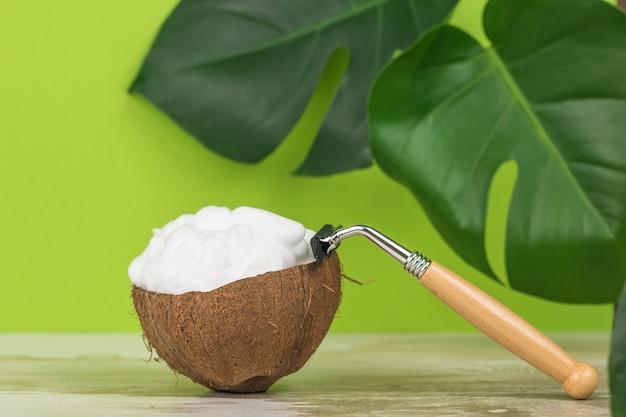 Rasoir vintage sur un bol de noix de coco sur fond de feuilles vertes.