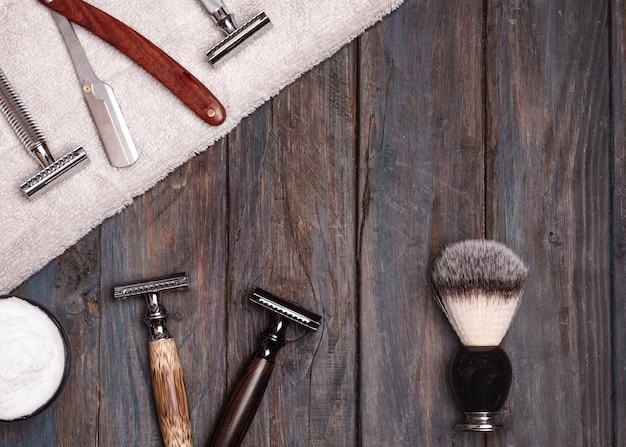Rasoirs, brosse, serviettes et mousse sur une table en bois.