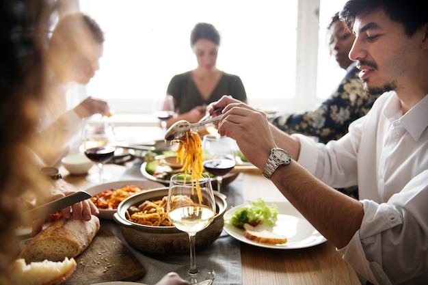 Rassemblement d'amis ayant de la nourriture italienne ensemble