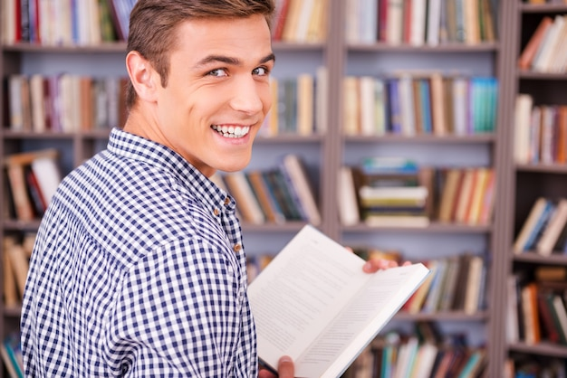 Rat de bibliothèque heureux. vue arrière d'un jeune homme heureux tenant un livre et regardant par-dessus l'épaule en se tenant debout contre une étagère