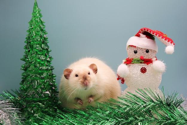 Un rat près d'un arbre de noël en jouet et d'un bonhomme de neige parmi des guirlandes.
