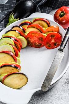 Ratatouille crue, plat de légumes traditionnel français. fond gris. vue de dessus.