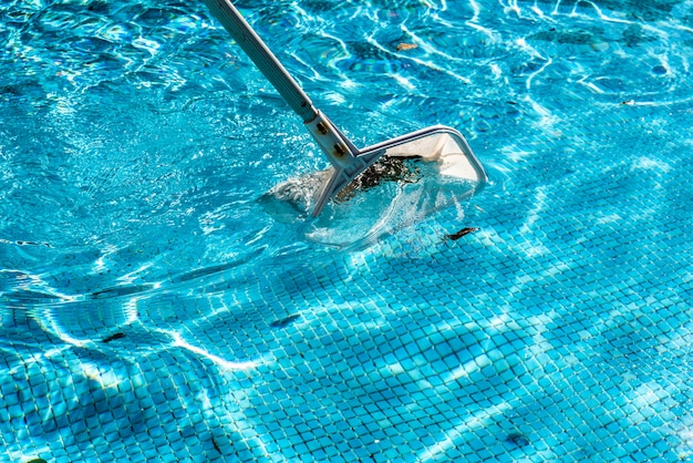 Râteau écumoire en forme de filet pour piscine en été.