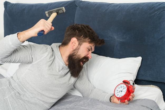 Rattrapez le sommeil manqué pendant le week-end. réveil matinal. étapes du sommeil. l'homme s'est réveillé mécontent de la sonnerie du réveil. même si vous dormez, vous pouvez vous réveiller avec l'impression de ne pas avoir dormi du tout.