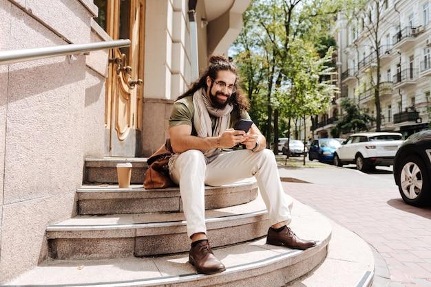 Ravi bel homme tapant un message alors qu'il était assis sur les escaliers avec son smartphone