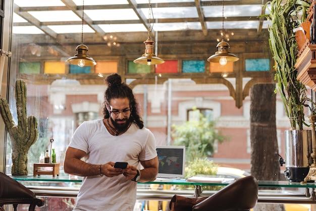Ravi bel homme tenant son smartphone tout en vérifiant les nouveaux messages