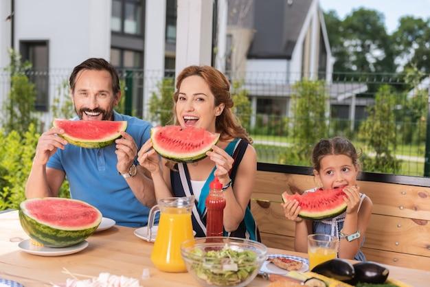 Ravi belle famille assis ensemble tout en dégustant des pastèques