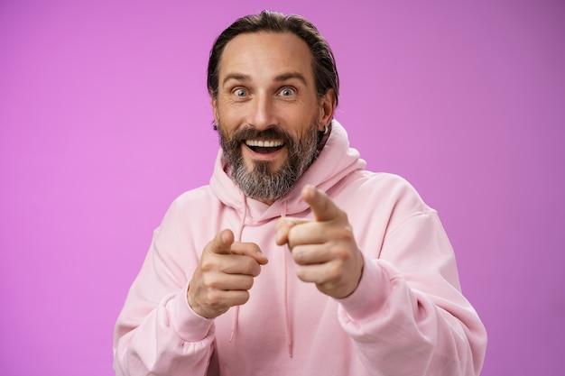 Ravi énergisé charismatique heureux heureux adulte bel homme barbu pointant la caméra souriant les yeux écarquillés regardant impressionné voir la personne célèbre exprimer la joie de la stupéfaction, fond violet.