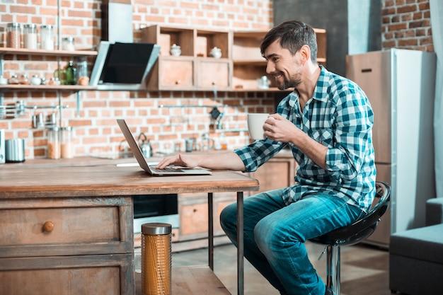 Ravi gentil homme heureux assis devant son ordinateur portable et souriant tout en prenant le thé