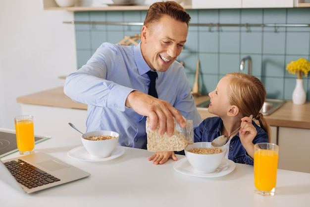 Ravi gentil père attentionné tenant une barre avec des céréales et l'ajoutant au bol de sa fille tout en prenant son petit-déjeuner avec elle