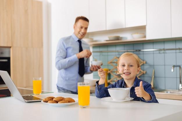 Ravi jolie fille mignonne tenant une cuillère et prendre le petit déjeuner
