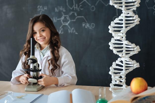 Ravi de mes futures responsabilités professionnelles. fille optimiste capable intelligente debout dans le laboratoire et bénéficiant d'un cours de médecine tout en participant au projet scientifique et en utilisant le microscope