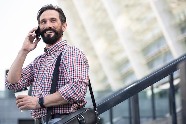 Ravi de te parler. heureux homme agréable souriant tout en parlant au téléphone à l'extérieur
