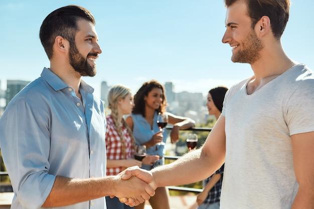 Ravi de vous rencontrer deux jeunes hommes heureux se serrant la main et souriant en se tenant debout