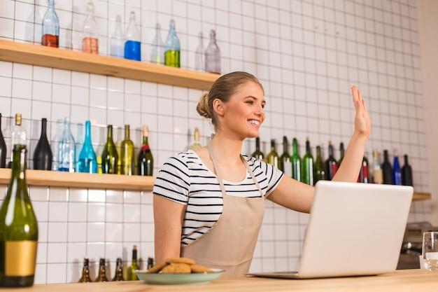Ravi de vous voir. enthousiaste belle femme positive debout au comptoir et agitant sa main tout en montrant l'hospitalité