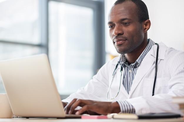 Ravie brune gardant les mains sur le clavier tout en regardant l'écran de son gadget