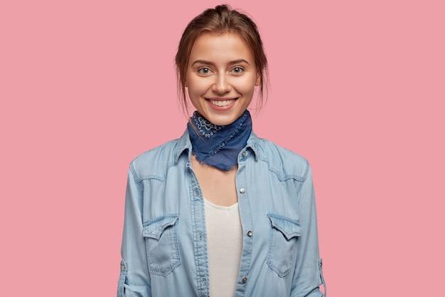 Ravie de jeune femme avec des lunettes posant contre le mur rose