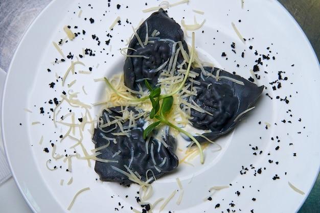 Ravioli à l'encre de seiche, sauce et fromage.