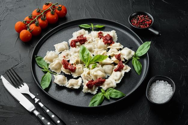 Raviolis appétissants à la sauce tomate, fromage et basilic avec basilic parmesan et tomate sur plaque noire, sur fond noir