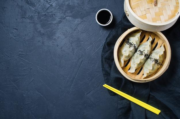 Raviolis coréens dans un steamer traditionnel, baguettes jaunes.
