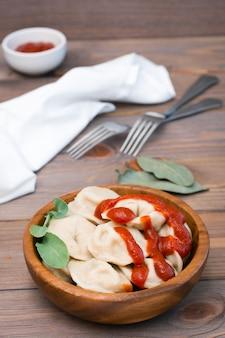 Raviolis cuits remplis de ketchup avec des feuilles de roquette dans un bol en bois sur la table