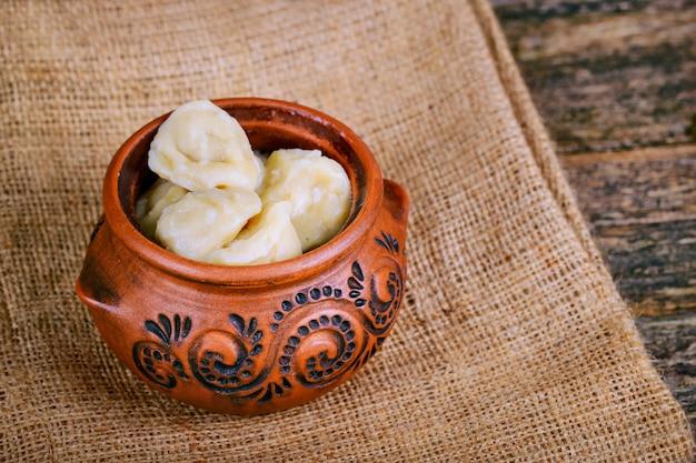 Raviolis faits maison décorés dans un pot en argile sur une serviette en lin sur un fond en bois.