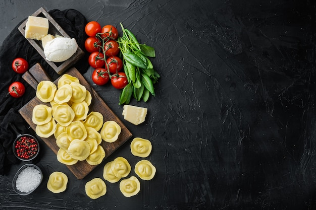 Raviolis faits maison avec du fromage mozzarella et du basilic, sur une planche à découper en bois, sur table noire, vue de dessus à plat