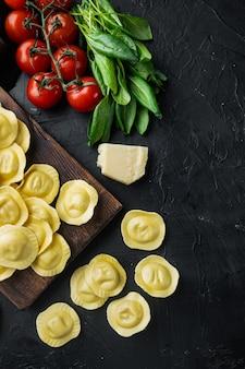 Raviolis faits maison avec fromage mozzarella et basilic, sur planche à découper en bois, sur fond noir, vue de dessus à plat, avec espace de copie pour le texte