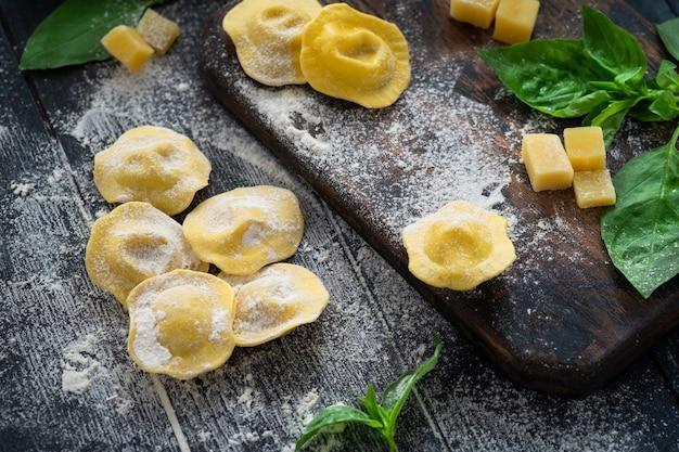 Raviolis italiens crus avec du parmesan et du basilic sur une planche de bois avec de la farine