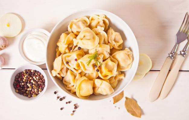 Raviolis italiens faits maison de boulettes de viande pelmeni russe dans le bol blanc.