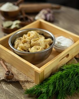 Raviolis russes à la crème sure, aneth et ail sur un plateau en bois