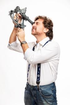 Ravissant capitaine souriant avec un sextant. mur blanc. verticale.