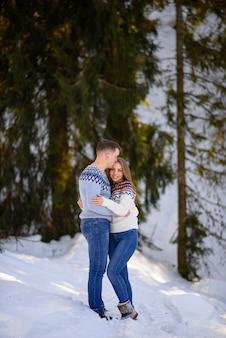Ravissant couple s'embrassant dans la forêt d'hiver.