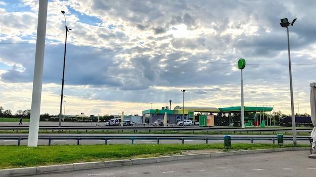 Ravitaillement des voitures sur l'autoroute dans le contexte d'un beau ciel avec des nuages et les rayons du soleil. concept de contraste de l'activité humaine et de la nature