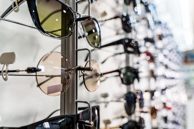 Raw de lunettes de soleil d'élégance de mode dans le magasin. vitrine avec lunettes de soleil dans un magasin ophtalmique moderne. fermer.