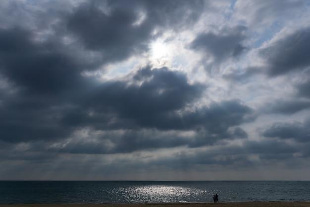 Rayon lumineux perce le nuage avec un couple traverser.