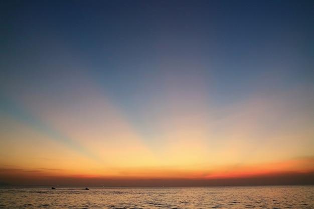 Rayon de soleil rayons crépusculaires en été avec les nuages la mer et l'île low key nature surface