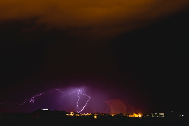 Rayons dans une tempête nocturne avec la lumière et les nuages.