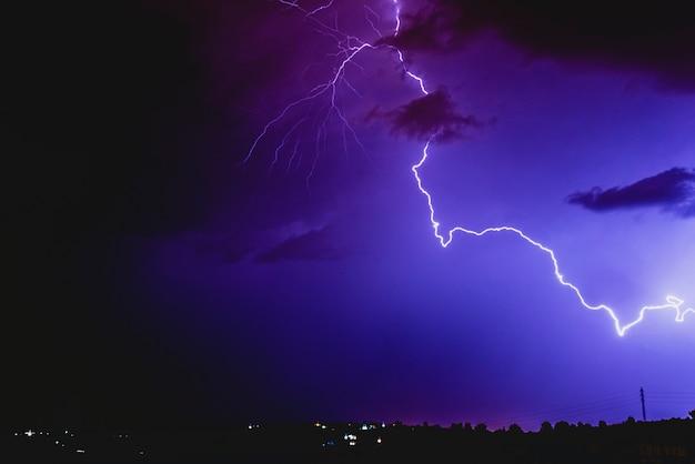 Rayons dans une tempête de nuit avec la lumière et les nuages.